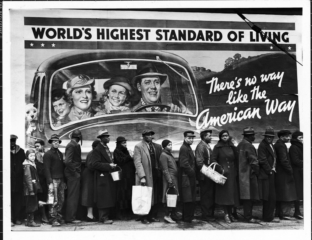 "African American flood victims lined up to get food and clothing from a Red Cross relief station in front of an ironic billboard extolling, ""World's highest standard of living/ there's no way like the American way."" (Photo by Margaret Bourke-White/The LIFE Picture Collection © Meredith Corporation)"