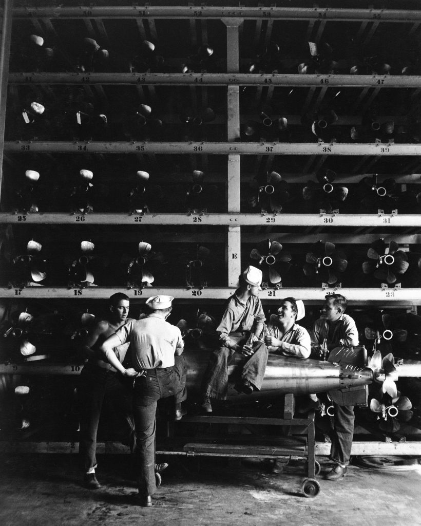 Group of torpedomen relaxing beneath rows of deadly torpedoes in torpedo shop, one man actually sitting on torpedo resting on gurney, during WWII. (Photo by Horace Bristol/The LIFE Picture Collection © Meredith Corporation)