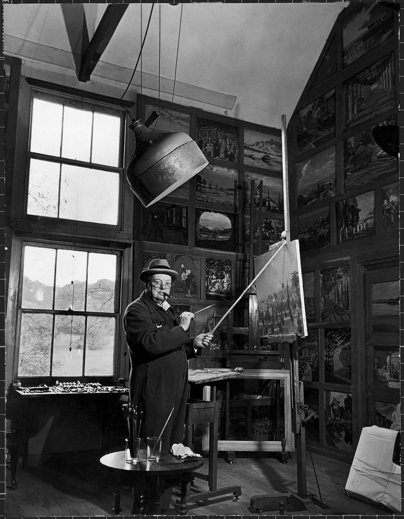 Former Prime Minister Winston Churchill smoking a cigar as he stands in his studio painting a landscape. (Photo by Hans Wild/The LIFE Picture Collection © Meredith Corporation)