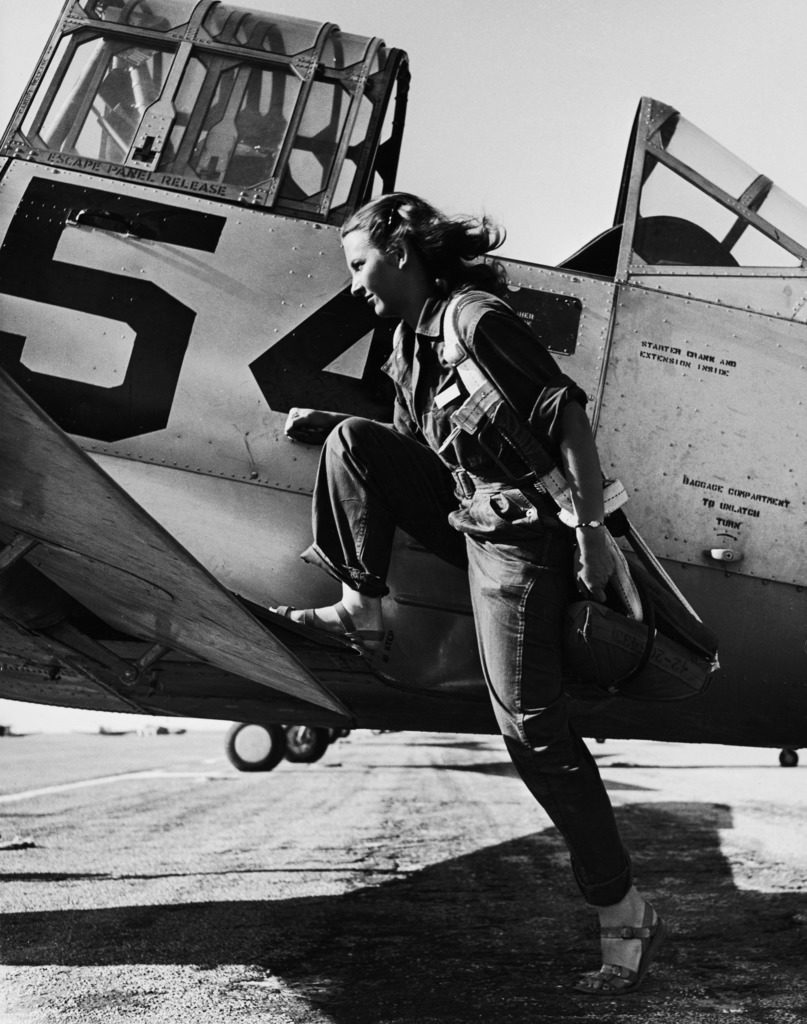 Female pilot of the US Women's Air Force Service posed with her leg up on the wing of an airplane. (Photo by Peter Stackpole/The LIFE Picture Collection © Meredith Corporation)