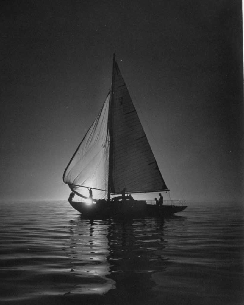 Full sails during a night sailboat race, with the sun peeking over the horizon. (Photo by Cornell Capa/The LIFE Picture Collection © Meredith Corporation)