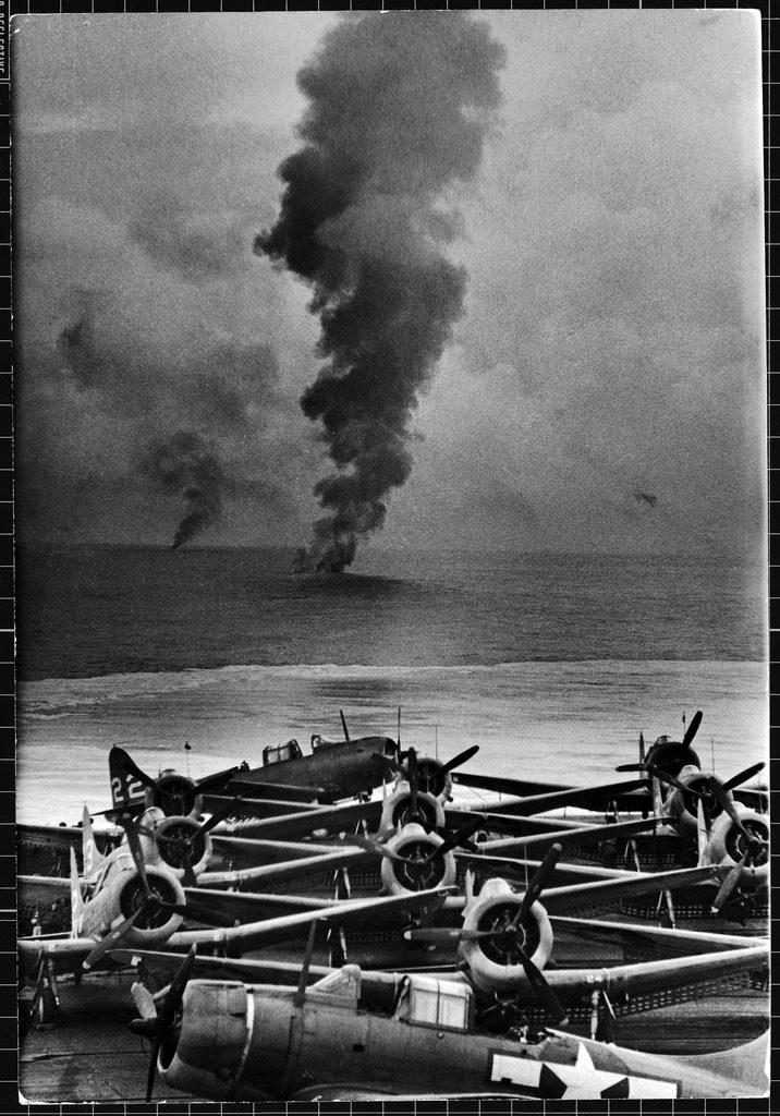 View from the rear deck of a US aircraft carrier, its planes parked on the flight deck, Japanese planes shot down by American fighter squadrons in the background. (Photo by William C. Shrout/The LIFE Picture Collection © Meredith Corporation)