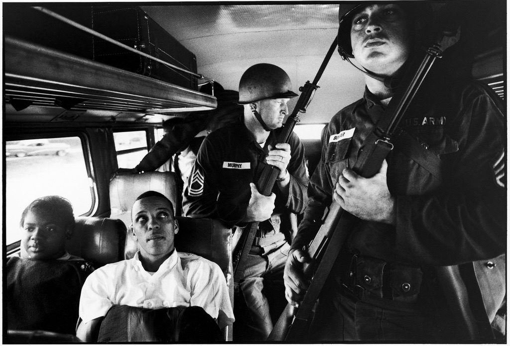 Freedom Riders Julia Aaron & David Dennis sitting on board interstate bus as they are escorted by two Mississippi National Guardsmen holding bayonets, on way from Montgomery, Alabama to Jackson, Mississippi. (Photo by Paul Schutzer/The LIFE Picture Collection © Meredith Corporation)