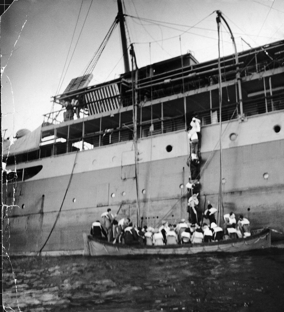 People climbing down a ladder, trying to board an already overfull lifeboat, as the SS Zam Zam sinks. (Photo by David E. Scherman/The LIFE Picture Collection © Meredith Corporation)