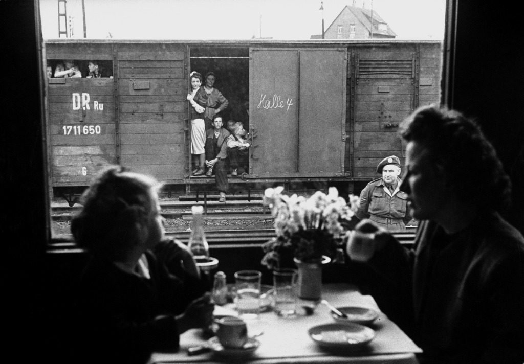 """Wife and daughter of a US soldier sitting in a first class dining car looking out at German """"expels"""" travelling in boxcars. (Photo by Walter Sanders/The LIFE Picture Collection © Meredith Corporation)"""