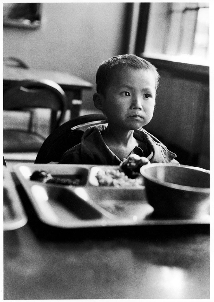 Korean orphan Kang Koo Ri sitting at table eating meal in orphanage after a US soldiers found him next to his dead mother. (Photo by Michael Rougier/The LIFE Picture Collection © Meredith Corporation)