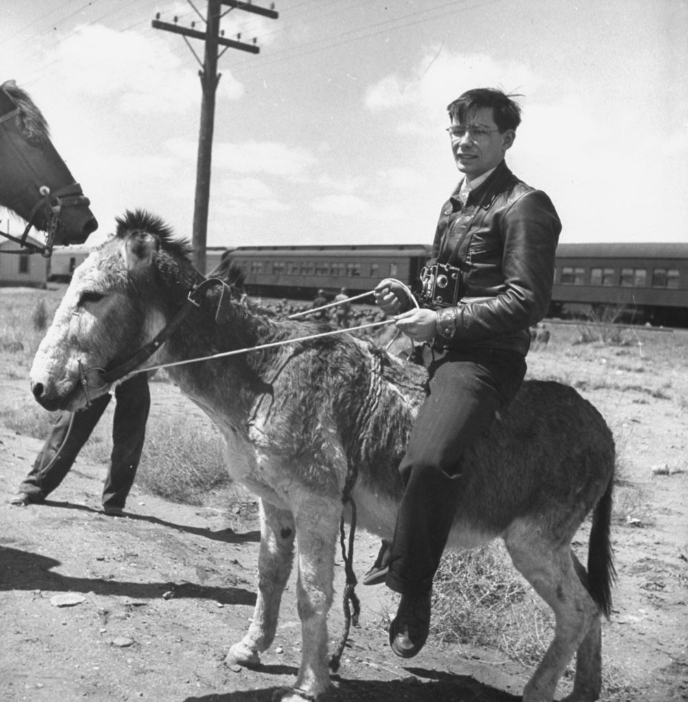 Myron Davis riding a burro while covering a story about a US troop train. (Photo by Myron Davis/The LIFE Picture Collection © Meredith Corporation)