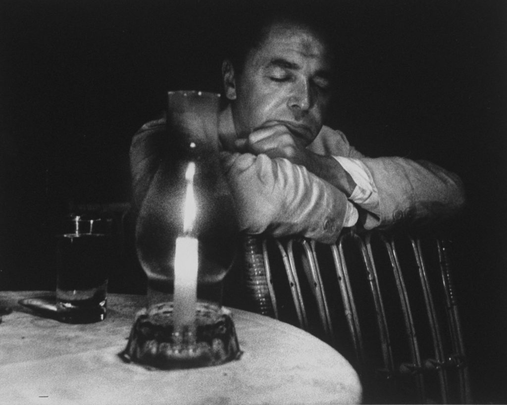 Eliot Elisofon, his eyes closed and his face illuminated by candle. (Photo by Gjon Mili/The LIFE Picture Collection © Meredith Corporation)