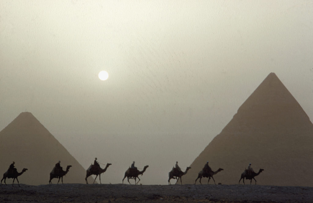 A camel caravan in front of the pyramids of Khefren and Cheops, also called the Great Pyramid. (Photo by Eliot Elisofon/The LIFE Picture Collection © Meredith Corporation)