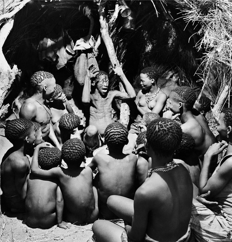 Bushman children sitting around their chief as he acts out a story, southern Kalahari Desert in central-southern Africa. (Photo by N.R. Farbman/The LIFE Picture Collection © Meredith Corporation)