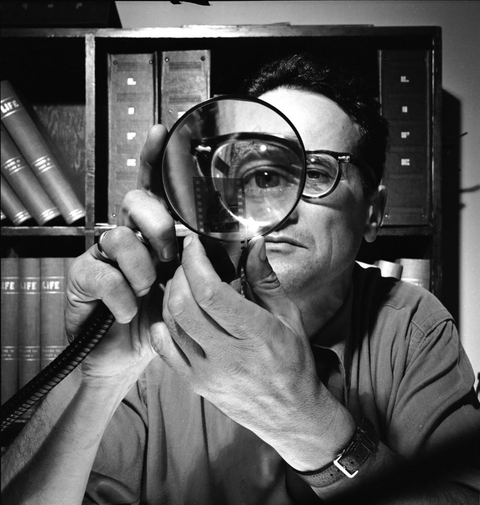Andreas Feininger looking at negatives with a magnifying glass. (Photo by Andreas Feininger/The LIFE Picture Collection © Meredith Corporation)