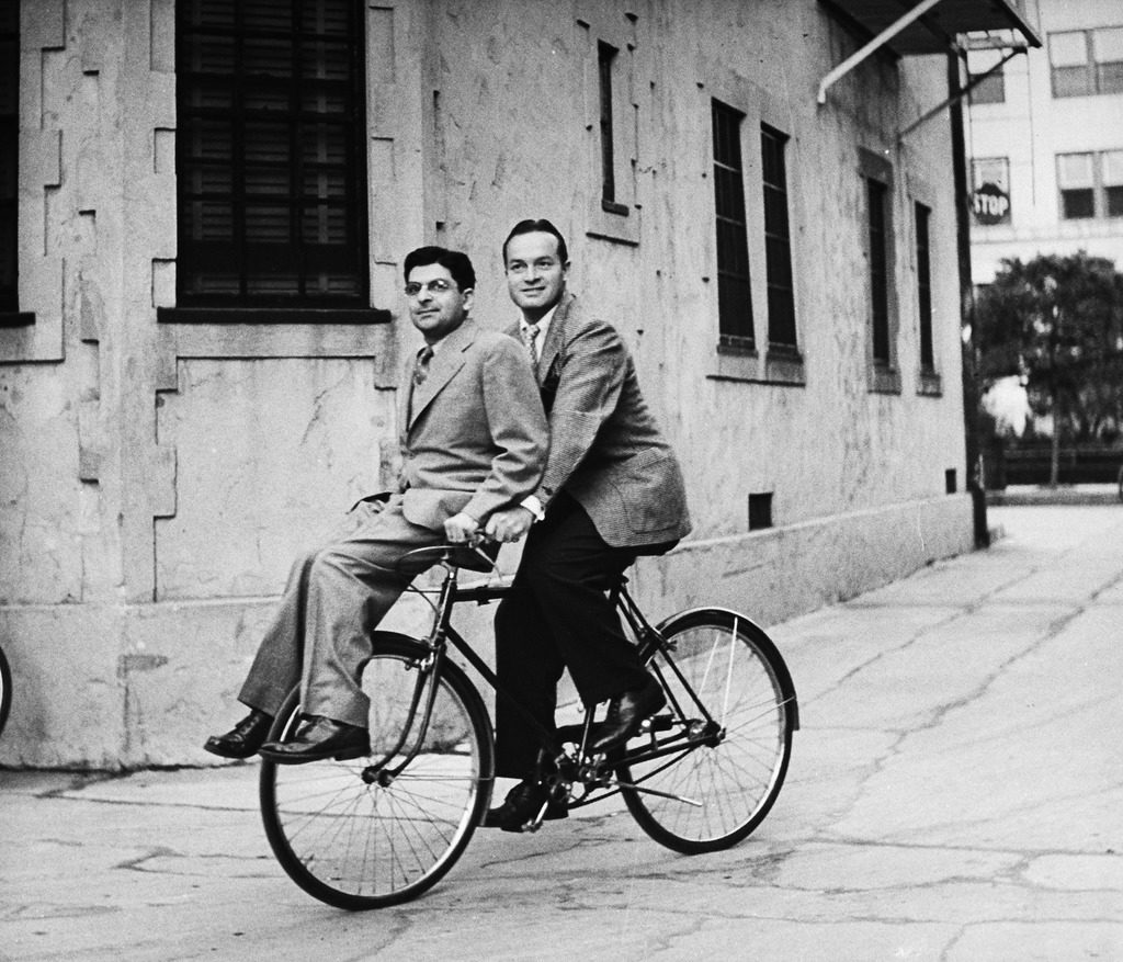 Columnist Sidney Skolsky (L) catching a ride on Bob Hope's (R) bicycle on his way from his dressing room to the sound stage. (Photo by John Florea/The LIFE Picture Collection © Meredith Corporation)
