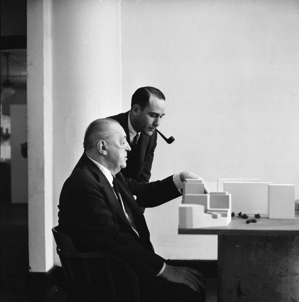 Realtor Herbert Greenwald and architect Mies van der Rohe consider a model of a Mies building, 1956.
