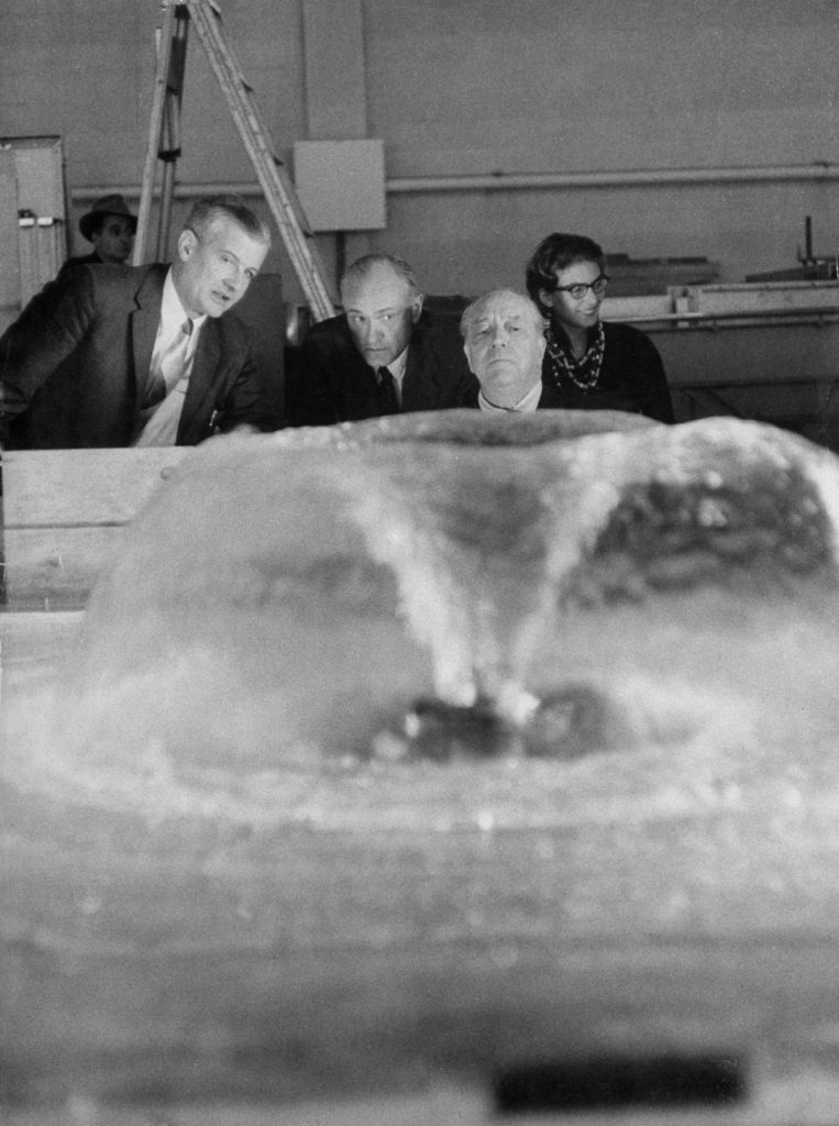 Testing a fountain in a laboratory at Massachusetts Institute of Technology, Mies and his Seagram associate, architect Philip Johnson (second from left), who planned fountain, decide to use two of them to decorate Seagram Plaza.