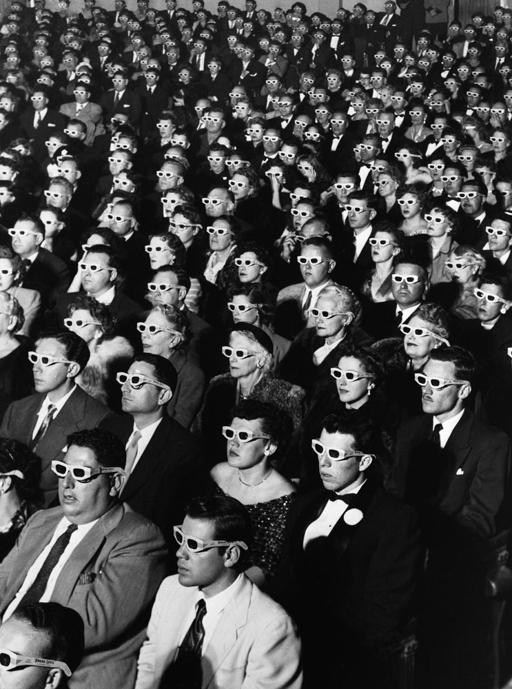 "Audience members sport 3-D glasses during the first screening of ""Bwana Devil,"" the first full-length, color 3-D movie, November 26, 1952, at the Paramount Theater in Hollywood."