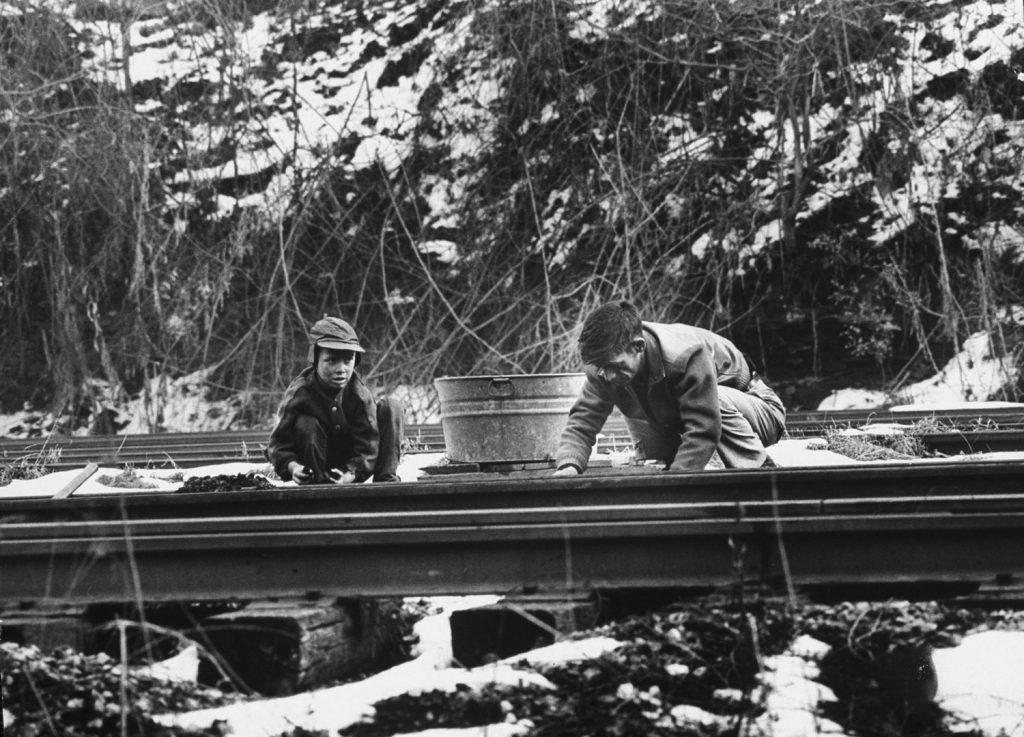Tearing with bare hands at frozen lumps of coal, Willard Bryant and his son Billy crouch between railroad tracks, scavenging fuel to heat their home. When the tub is full, they will drag it to the hill where they live, reload the coal into bags and carry it on their backs to the house.