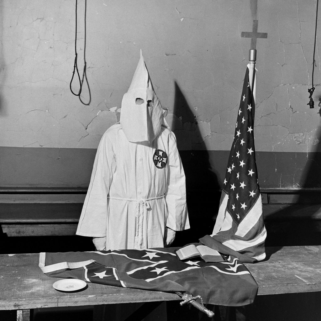 A Ku Klux Klan member demonstrates ritualistic aspects of a KKK meeting, Georgia, May 1946.