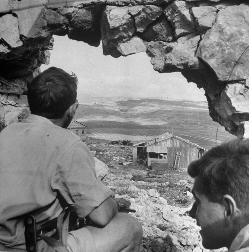 Two men peer out of a hole in a bombed building, shortly after the establishment of the state of Israel, May 1948.