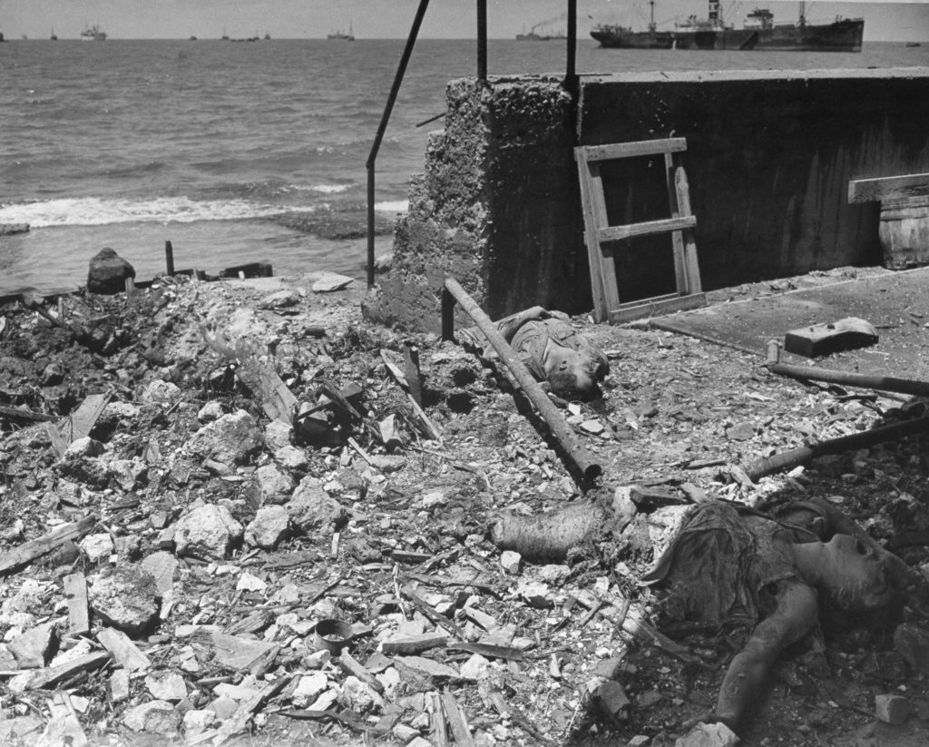 After an Arab air raid, bodies of dead Jews lie in the rubble along the Tel Aviv waterfront.