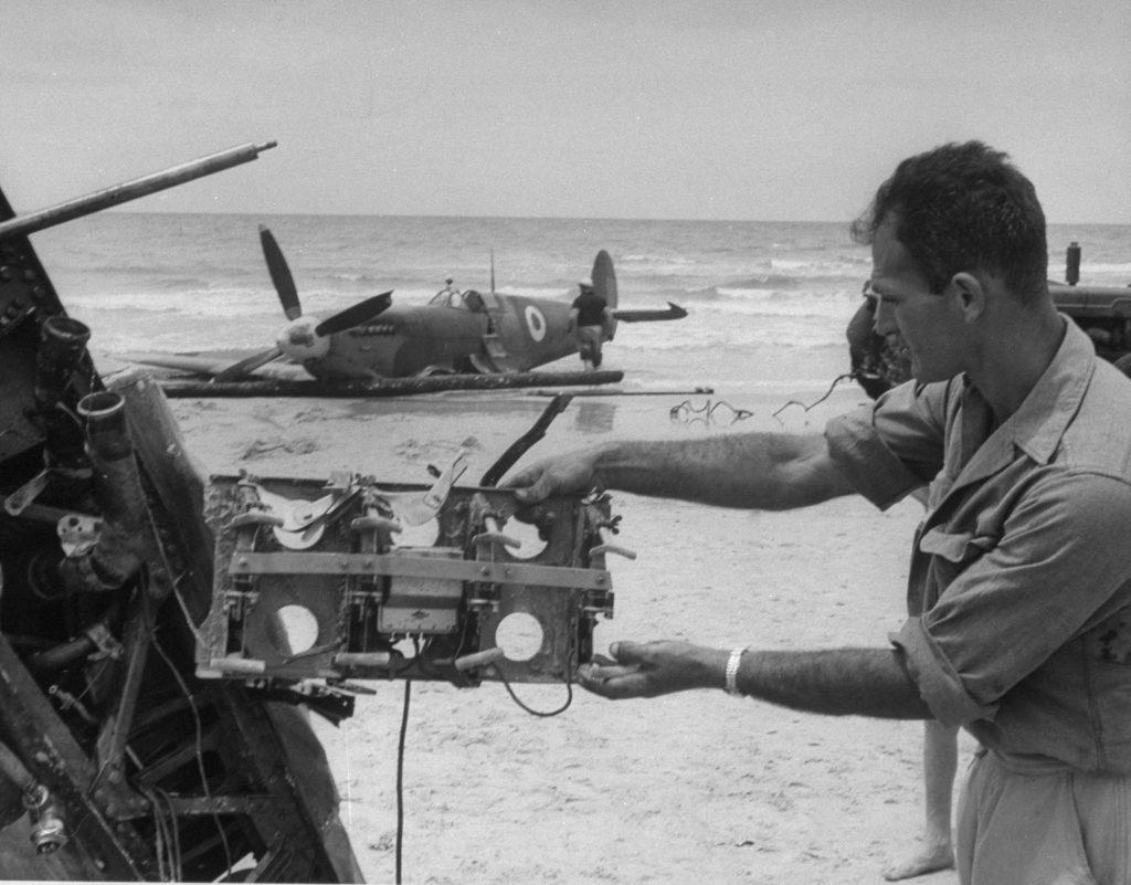 Haganah [Jewish paramilitary] soldier examines souvenir from Egyptian Spitfire shot down by Jews on Tel Aviv beach.