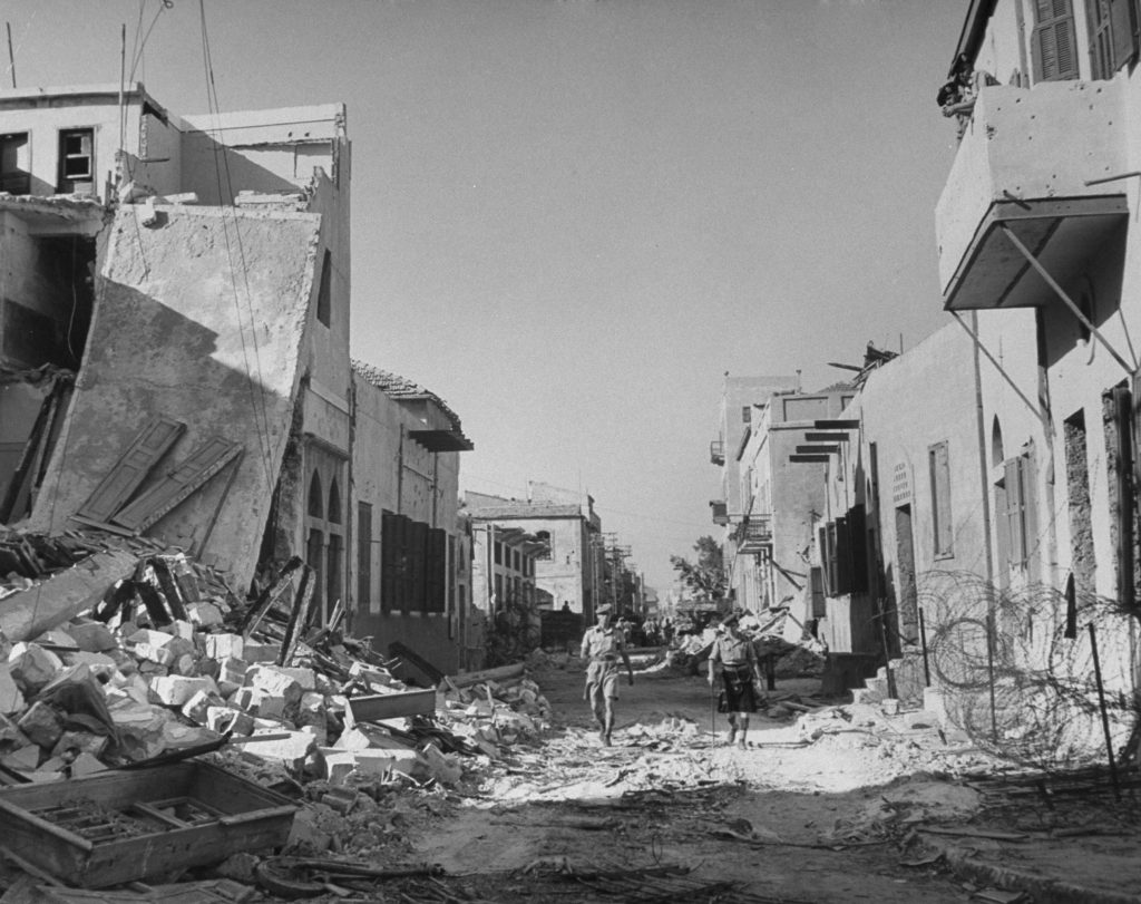 Soldiers walk down a ruined street, shortly after the establishment of the state of Israel, exact location unknown, May 1948.