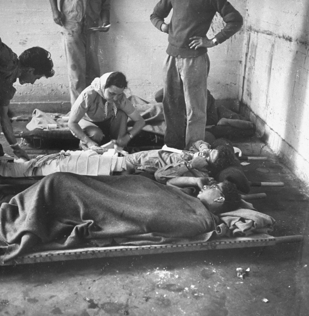 Israeli wounded being cared for in forward first aid station, shortly after the establishment of the state of Israel, exact location unknown, May 1948.