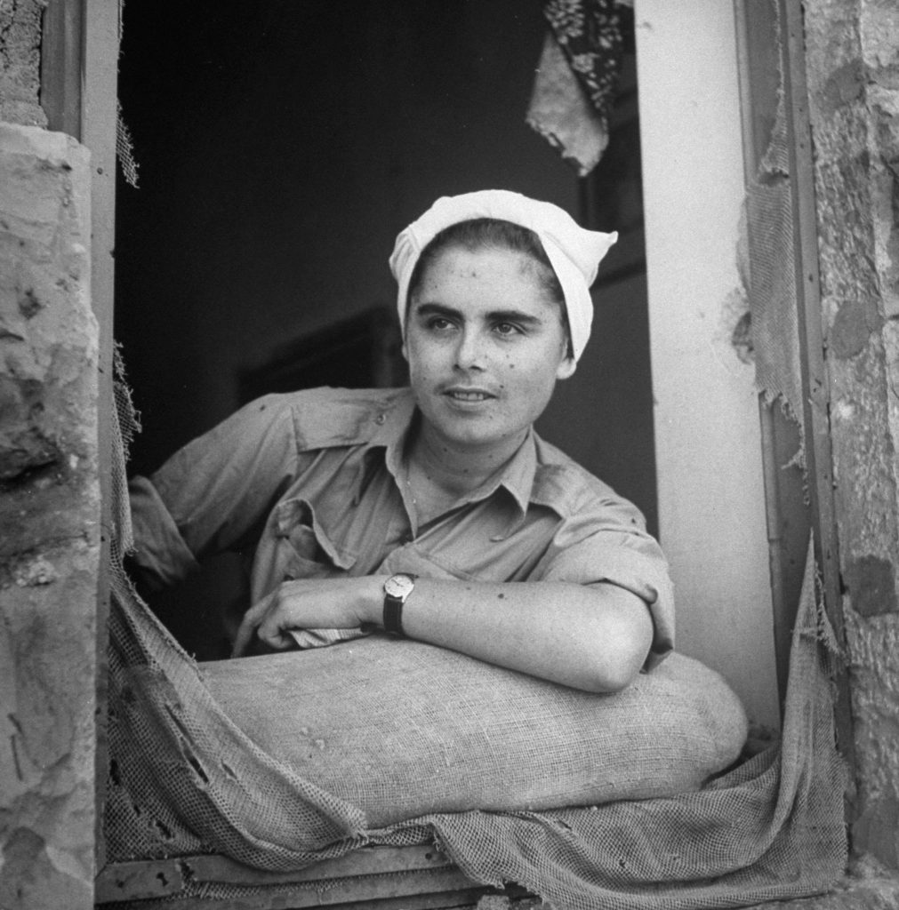 A young woman looks out a battered window shortly after the establishment of the state of Israel, exact location unknown, May 1948.