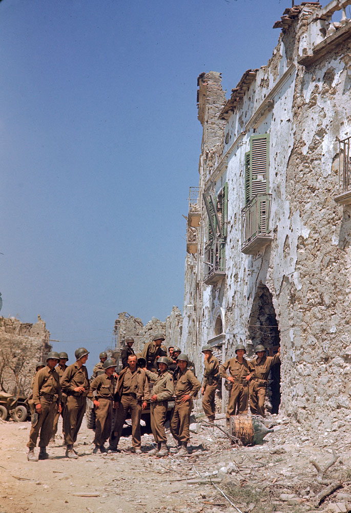 American troops stand in front of a bombed-out building during the drive towards Rome, WWII.