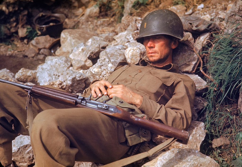 An American soldier sleeps on a pile of rocks during the drive towards Rome, 1944.
