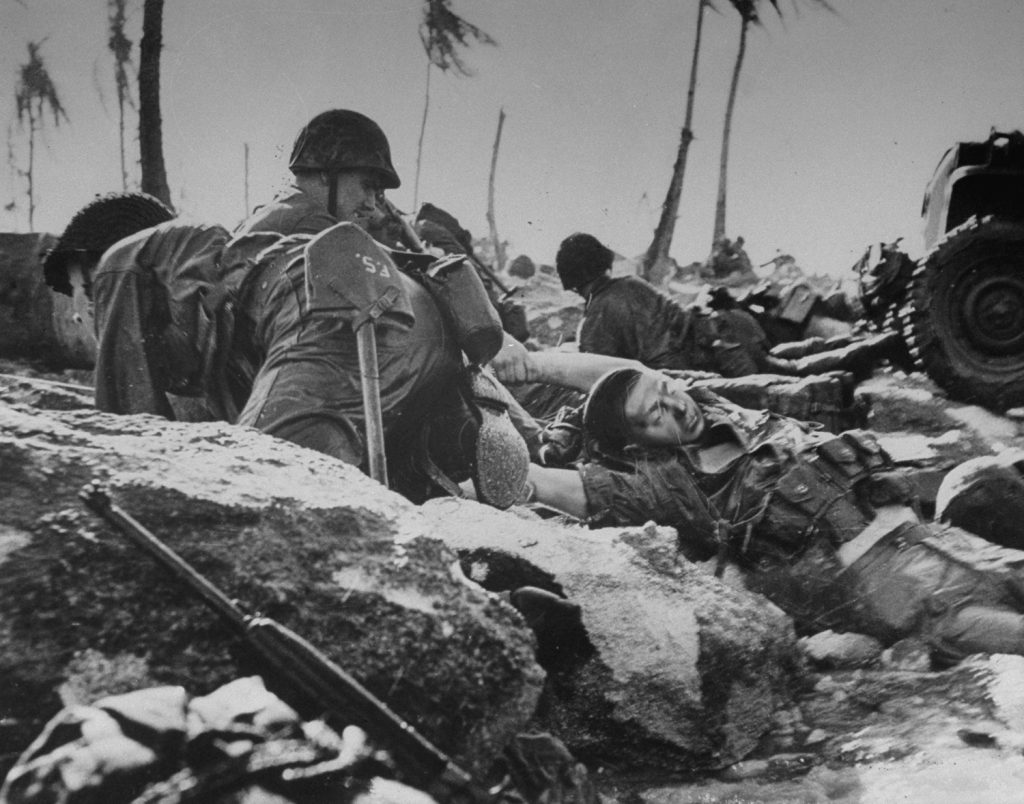 On the coral beach of Eniwetok's Engebi Island, a Marine drags a dead comrade out of the surf.