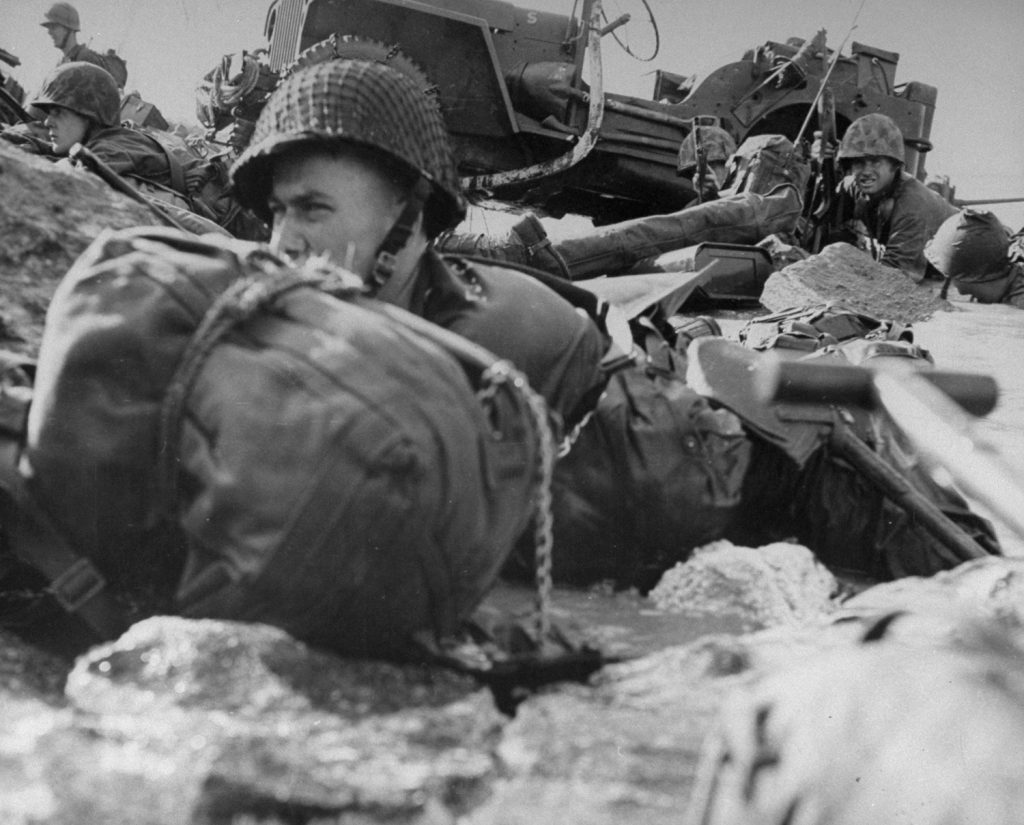 Marines hug sharp coral of beach, with pillbox only 12 yards in front of them. Strock, still lying in the water, has poked camera just over low pile of coral. Men finally edged back into the surf and moved cautiously down beach to flank pillbox. Marine in the background at upper left shows dangerous curiosity.