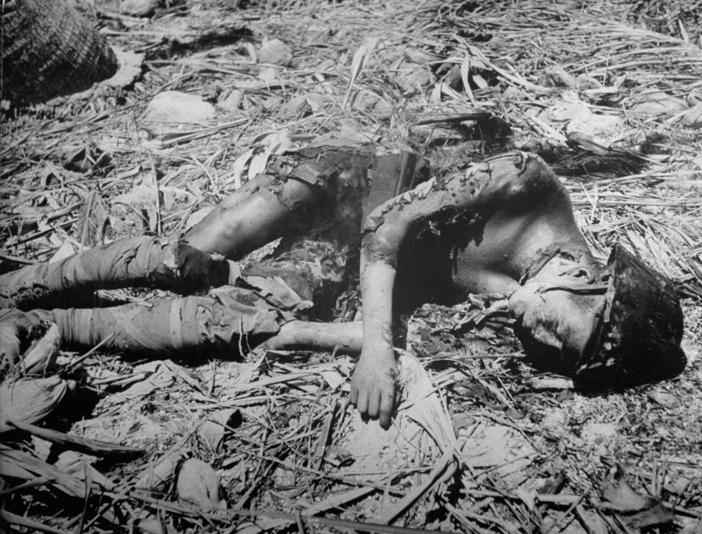 """Caption from back of the print of this photograph in the LIFE archives: """"Dead Jap [sic] with smoke still rising from his stomach where flamethrower boiled him open."""""""