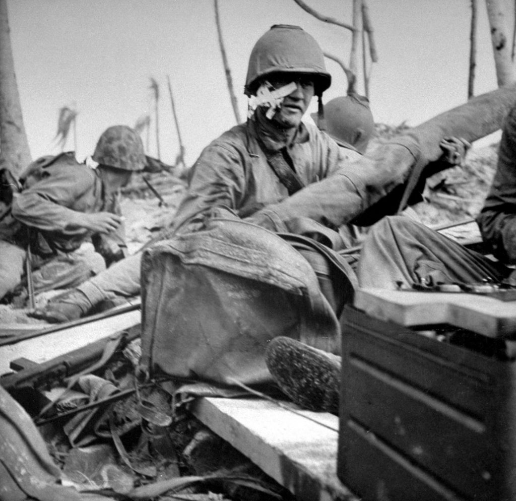 """Caption from back of the print of this photograph in the LIFE archives: """"Wounded Marine still fighting though his face is shot open, just after landing."""""""