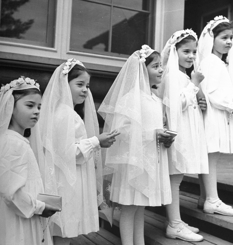 """A view of the """"Dionne Quintuplets"""" posing in their confirmation dresses on day of their first Holy Communion, 1940."""