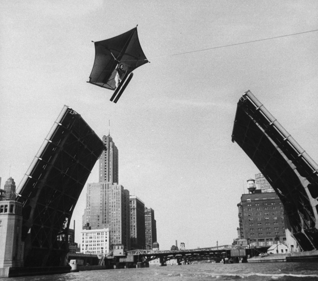 Stunt man Jack Wylie flying over the Chicago River, 1958.
