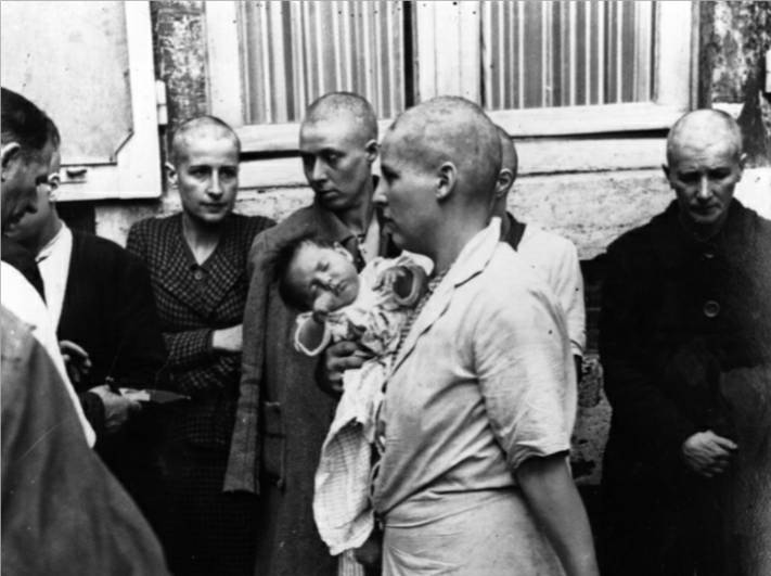 A French woman collaborator and her baby, whose father is German, returns to her home after having her head shaven following the capture of Chartres by the Allies, August 1944.