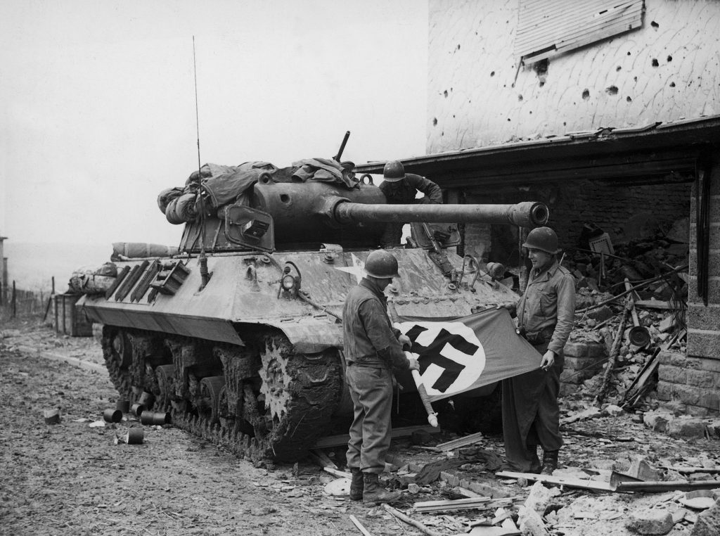 American soldiers of Patton's Third Army roll up a Nazi flag they have taken as a trophy after the capture of Bitburg, February 1945.