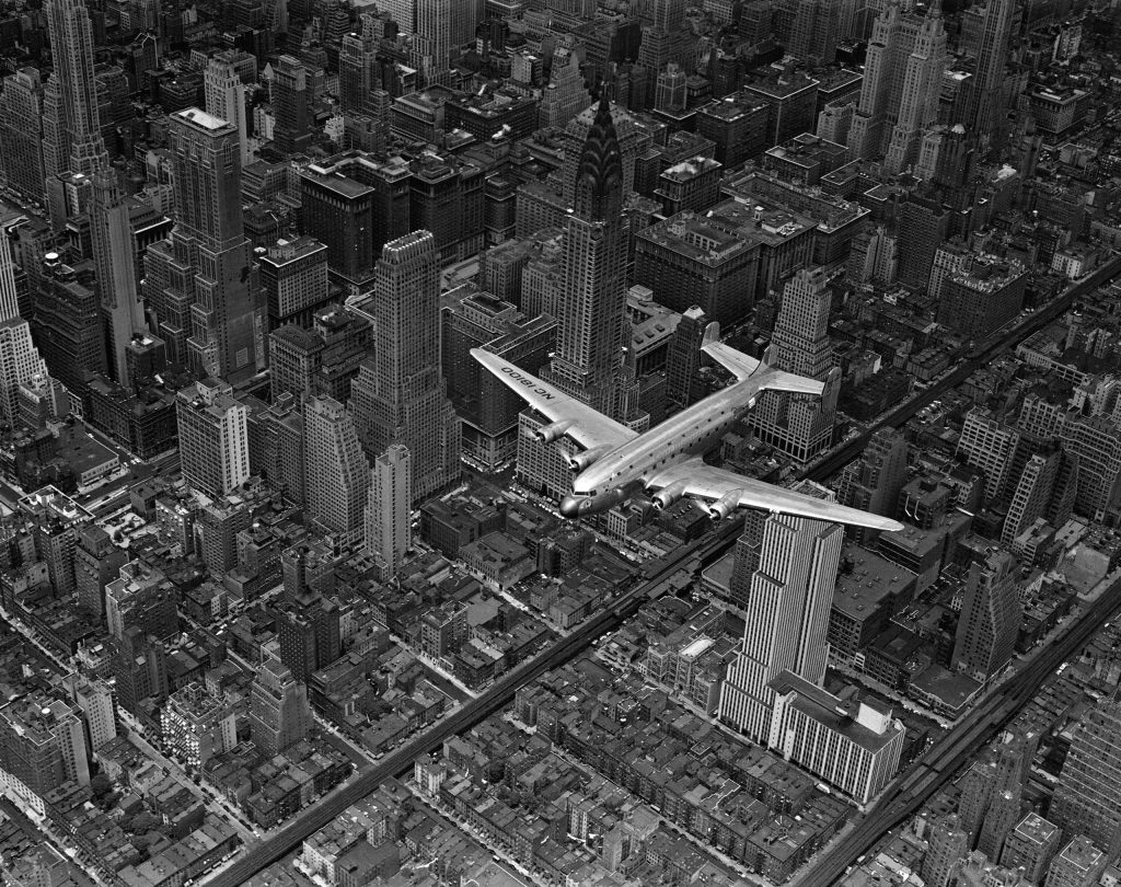 Aerial view of a DC-4 passenger plane flying over midtown Manhattan. An almost identical photograph from this shoot was published in the June 19, 1939, issue of LIFE.