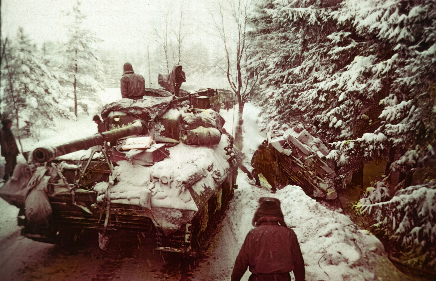 An American tank moves past another gun carriage which slid off an icy road in the Ardennes Forest during the Battle of the Bulge, Dec. 20, 1944.