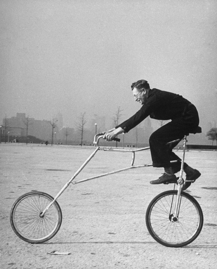 Inventor Maurice Steinlauf riding eccentric bike with roving front wheel.