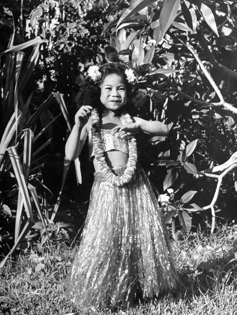 Young girl dancing in hula skirt.