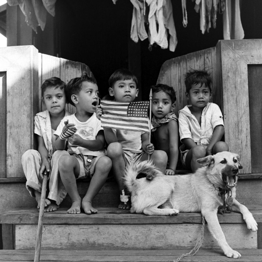 Children with American flag hanging out on a front porch.