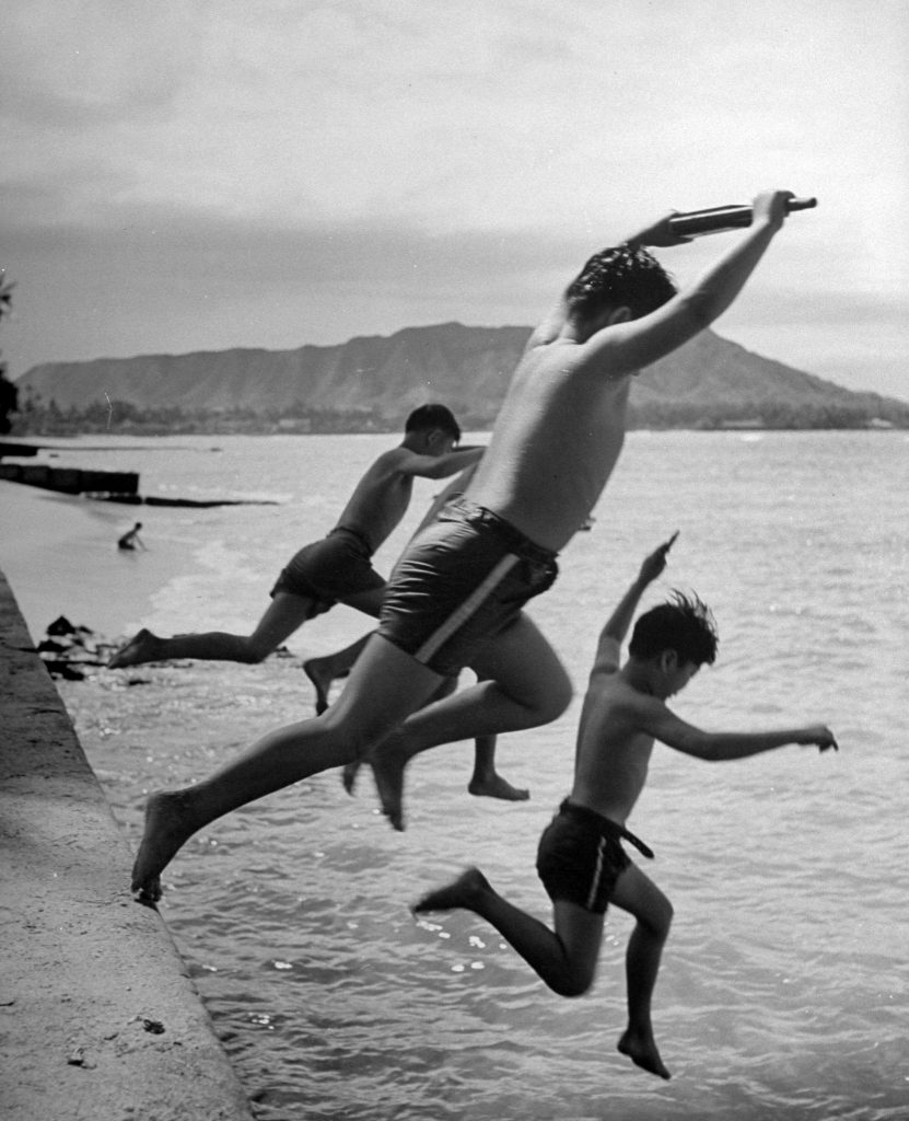 Japanese boys jumping from sea wall while playing as soldiers in American army.