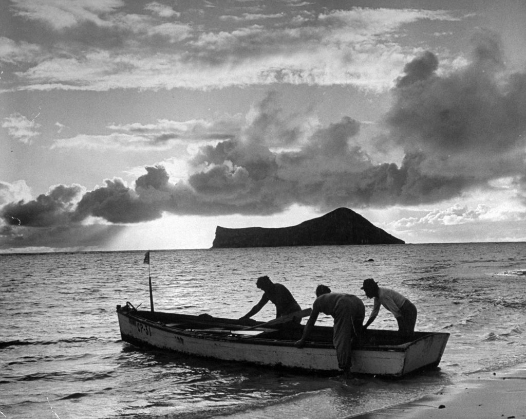 At dawn Hawaiians put out to sea to pull in their fish nets. By law, their boat flies the American flag at bow.