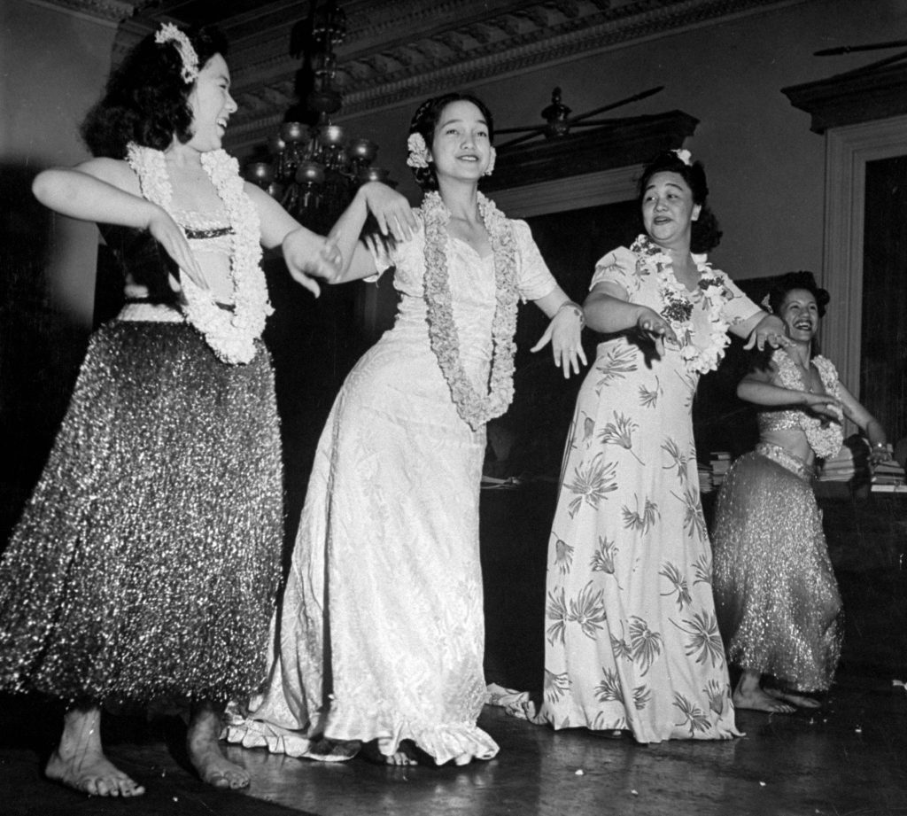 Girls dressed in hula skirts dancing inside.