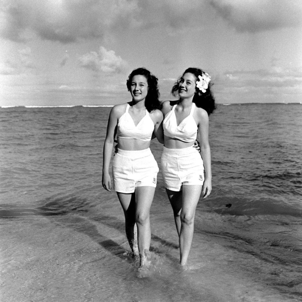 Two Hawaiian girls walking along the shore.