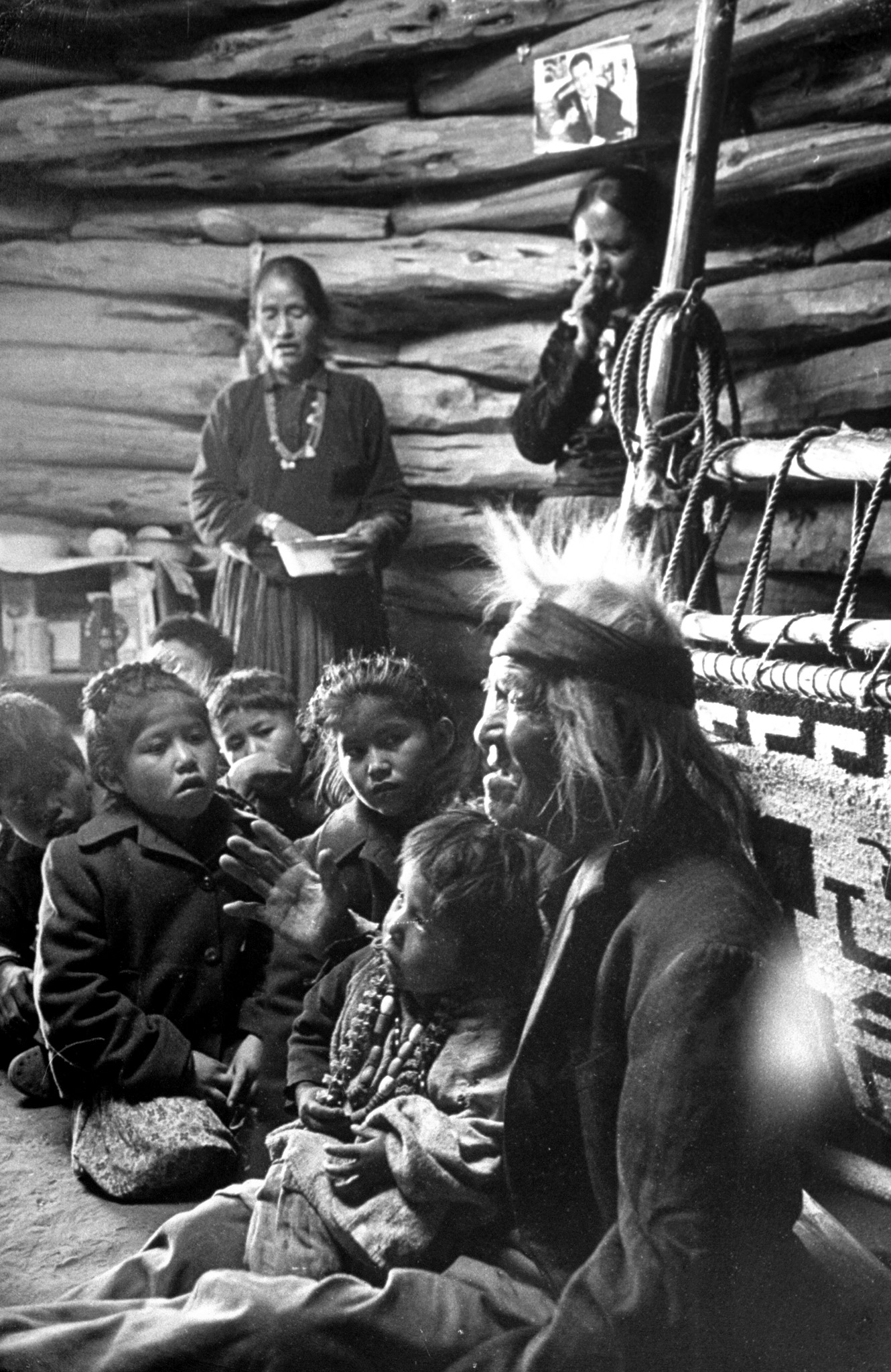 Seated close to the evening fire, old man Gray Mountain, 91, tells his small grandchildren legends about the early days of the Navajo people.