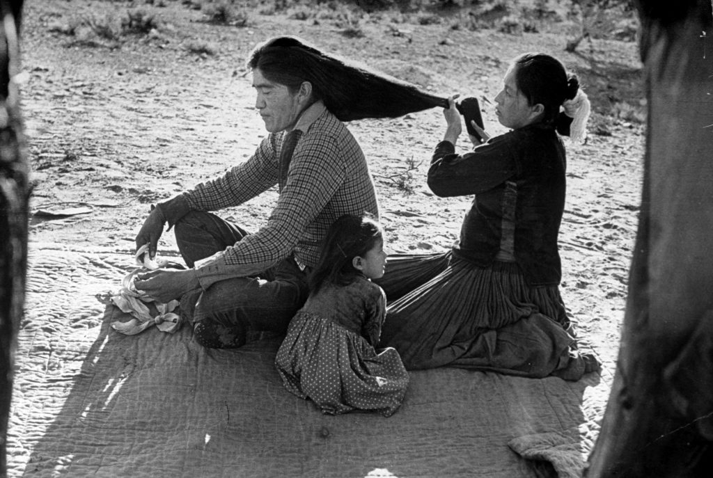 Yellowsalt's son has his hair brushed by wife. Nowadays many young Navajos wear their hair short.