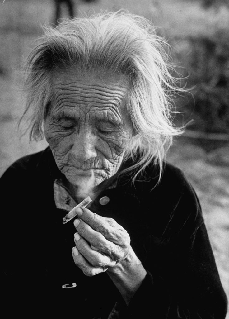 A Navajo woman smoking a hand rolled cigarette.