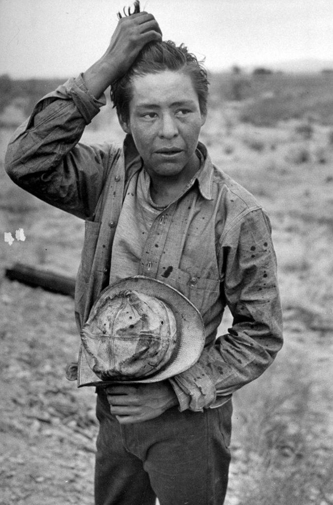 A Navajo boy running his fingers through his hair.